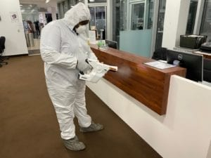 Man in hazmat suit disinfecting desk
